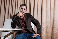 Middle Eastern businessman in the office. Middle Eastern businessman standing at his desk thinking royalty free stock image