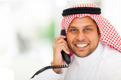 Middle eastern businessman telephone. Smiling middle eastern man answering telephone in office Stock Photo