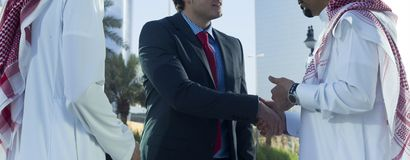 Middle eastern and caucasian businessmen shaking hands outdoor stock photography