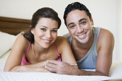 A Middle Eastern couple lying on a bed Royalty Free Stock Photo