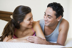 A Middle Eastern couple lying on a bed Royalty Free Stock Photography