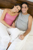 A Middle Eastern couple lying on a bed Royalty Free Stock Photos