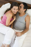 A Middle Eastern couple lying on a bed Stock Photography