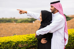 Middle eastern couple pointing. Cheerful young middle eastern couple pointing outside their house Royalty Free Stock Photo