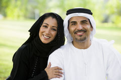 A Middle Eastern couple sitting in a park Stock Photos