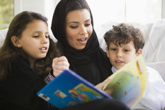 A Middle Eastern family reading a book together.  Stock Photography