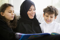 A Middle Eastern family reading a book together.  Stock Photo