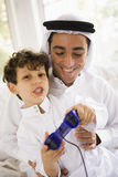 A Middle Eastern father and son playing. A video game stock photo