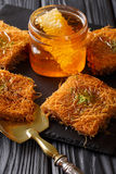 Middle Eastern food: kunafeh with pistachios and honey close-up. Royalty Free Stock Images