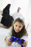 A Middle Eastern girl playing a video game Stock Photo