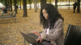 Middle Eastern girl is sitting on a bench in an autumn park and typing text on the laptop. Mixed race Girl is sitting on a bench in an autumn park and typing stock footage