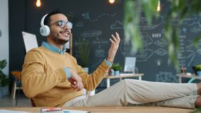 Middle Eastern guy enjoying music in headphones singing moving arms at work