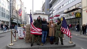 Middle Eastern / Indian Tourists posing for pictures at the Checkpoint Charlie attraction in Berlin Germany. 4K UHD footage of Berlin, Germany - March 23, 2019 stock video footage