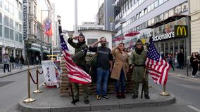 Middle Eastern / Indian Tourists posing for pictures at the Checkpoint Charlie attraction in Berlin Germany. 4K UHD footage of Berlin, Germany - March 23, 2019 stock footage