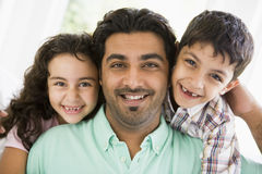 A Middle Eastern man with his children. Smiling to camera royalty free stock image