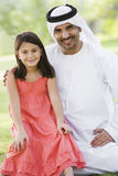 A Middle Eastern man and his daughter in a park stock photos