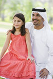 A Middle Eastern man and his daughter in a park Royalty Free Stock Image