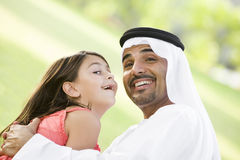 A Middle Eastern man and his daughter in a park. A Middle Eastern man and his daughter sitting in a park stock image
