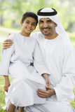 A Middle Eastern man and his son sitting in a park. Smiling Royalty Free Stock Images