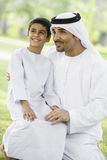 A Middle Eastern man and his son sitting in a park stock photo