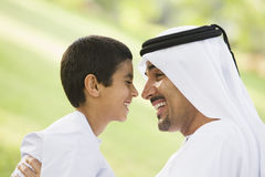 A Middle Eastern man and his son sitting in a park stock photos