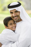 A Middle Eastern man and his son sitting in a park. Smiling royalty free stock photo