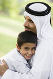 A Middle Eastern man and his son sitting in a park.  royalty free stock photography