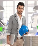 Middle-eastern man leaving architect office. Middle-eastern architect leaving office, carrying laptop and protective helmet royalty free stock image