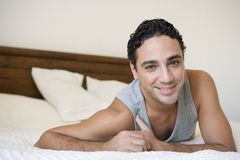 A Middle Eastern man lying on a bed Stock Images