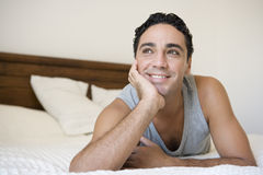 A Middle Eastern man lying on a bed royalty free stock photography
