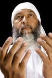 Middle Eastern Man Praying. Stock image or middle eastern man praying over black background, selective focus on man stock image