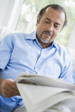 A Middle Eastern man reading a newspaper at home.  royalty free stock photography