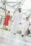 A Middle Eastern man with two children shopping Stock Image