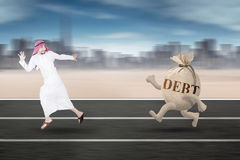 Middle eastern person running away from debt. Photo of a middle eastern entrepreneur running away from a money bag with debt words on the street Stock Photos