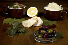Middle Eastern Spread. Middle Eastern appetizer spread including tabouleh, hummas, dolma, fatayees and spiced olives on a wooden table Stock Photos