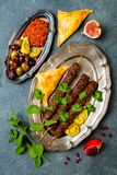 Middle Eastern traditional dinner. Authentic arab cuisine. Meze party food. Lamb kebab, sambusek, muhammara. Top view, flat lay, overhead stock images