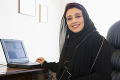 A Middle Eastern woman. Sitting in front of a computer Stock Photos