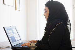 Middle Eastern woman on computer. At home Royalty Free Stock Photo