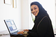 A Middle Eastern woman on a computer. A Middle Eastern woman sitting in front of a computer at home Royalty Free Stock Photos