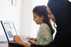 A Middle Eastern woman and daughter at home. A Middle Eastern woman and her daughter sitting in front of a computer Royalty Free Stock Images