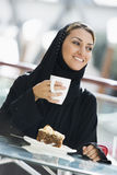 A Middle Eastern woman enjoying a meal Stock Image