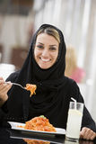 A Middle Eastern woman enjoying a meal Royalty Free Stock Images