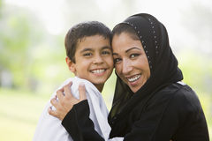 A Middle Eastern woman and her son. Sitting in a park Royalty Free Stock Image