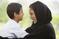 A Middle Eastern woman and her son in a park. A Middle Eastern woman and her son sitting in a park Royalty Free Stock Image
