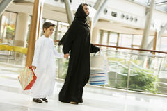 A Middle Eastern woman and her son in shopping stock photo