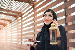 Middle Eastern Woman Holding Dates for Ramadan. Middle Eastern woman in traditional abaya holding dates and Arabian lantern Royalty Free Stock Image