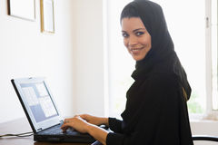 A Middle Eastern woman at home. A Middle Eastern woman sitting in front of a computer at home Stock Images