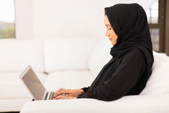Middle eastern woman laptop. Pretty young middle eastern woman using laptop at home Stock Image