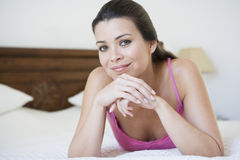 A Middle Eastern woman lying on a bed Royalty Free Stock Image