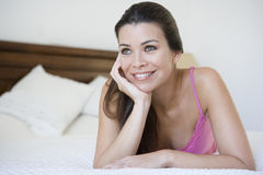 A Middle Eastern woman lying on a bed Royalty Free Stock Photos